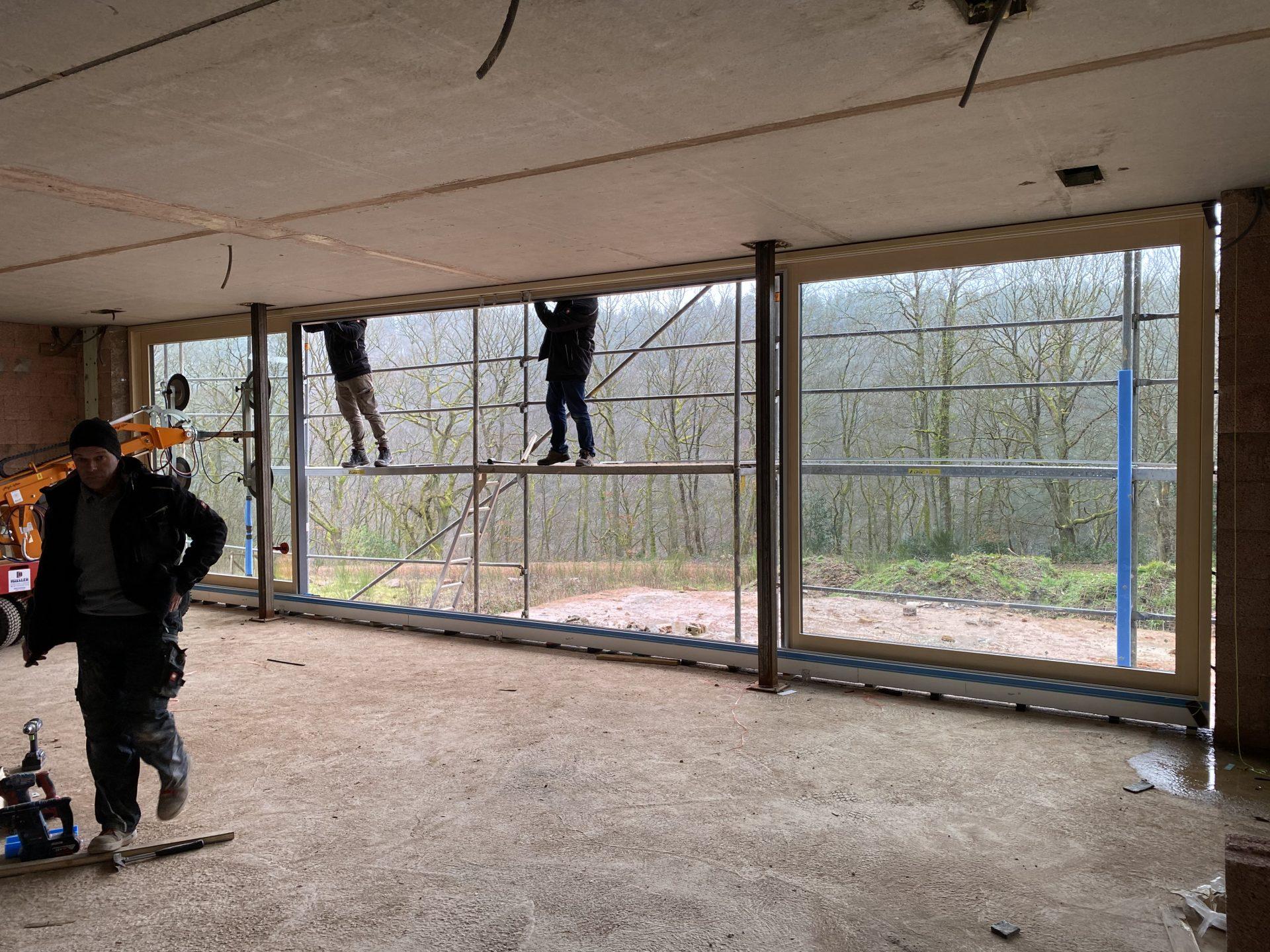 Großes Fensterelement mit Hebe-Schiebetüren während der Montage